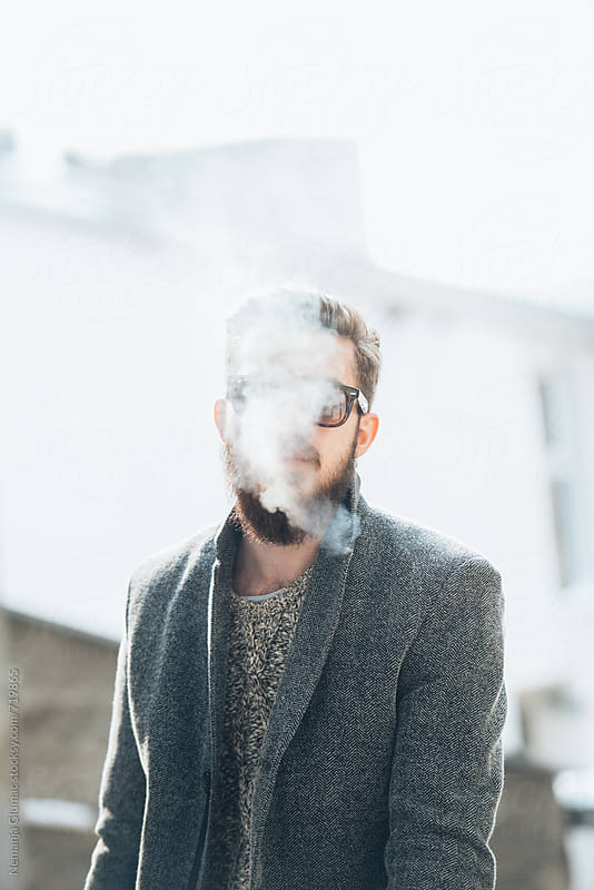 Man With Beard Smoking Outdoors by Nemanja Glumac for Stocksy United