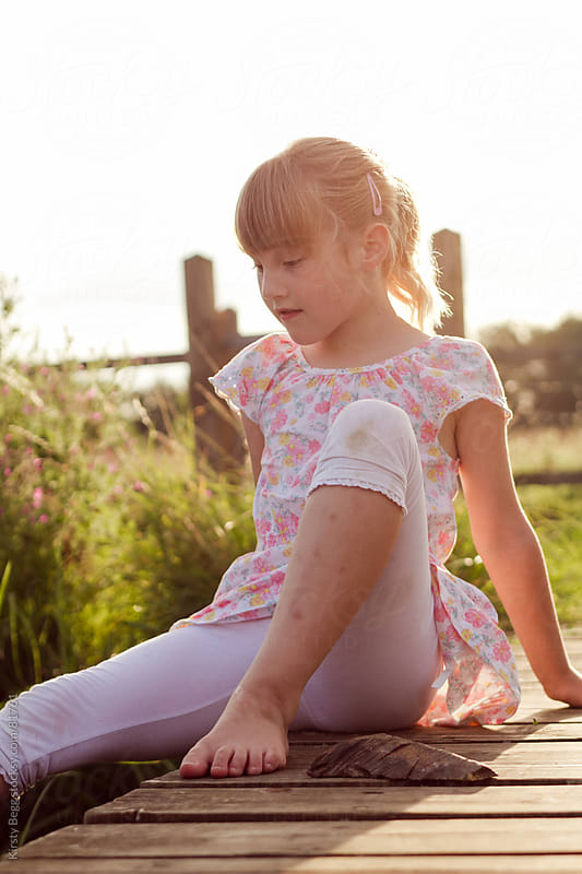 Girl sitting in evening light on nature reserve boardwalk by Kirsty Begg for Stocksy United