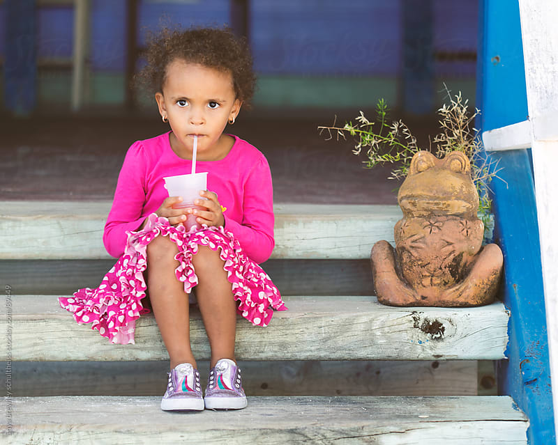 Young girl sits next to a stone frog as she sips a drink. by anya brewley schultheiss for Stocksy United
