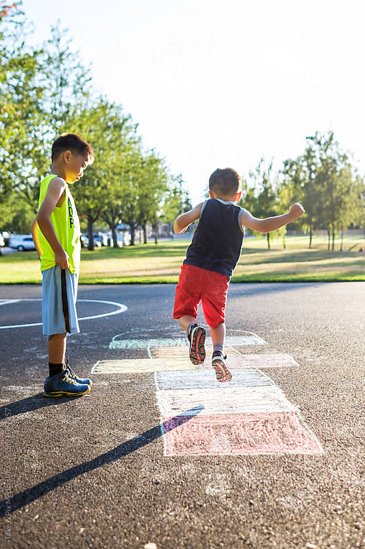 Asian kids playing hopscotch in the playground by Suprijono Suharjoto for Stocksy United
