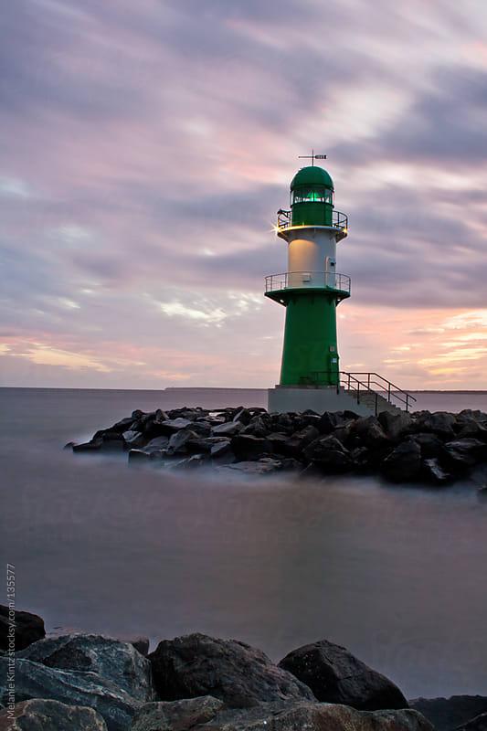 Long exposure image of a lighthouse at sunrise by Melanie Kintz for Stocksy United
