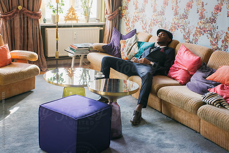Fashionable Young Black Man Napping in Bright Living Room by VISUALSPECTRUM for Stocksy United