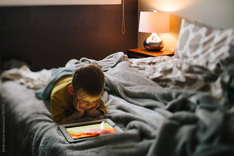 a little boy watching a video on his parents' bed  by Sarah Lalone for Stocksy United