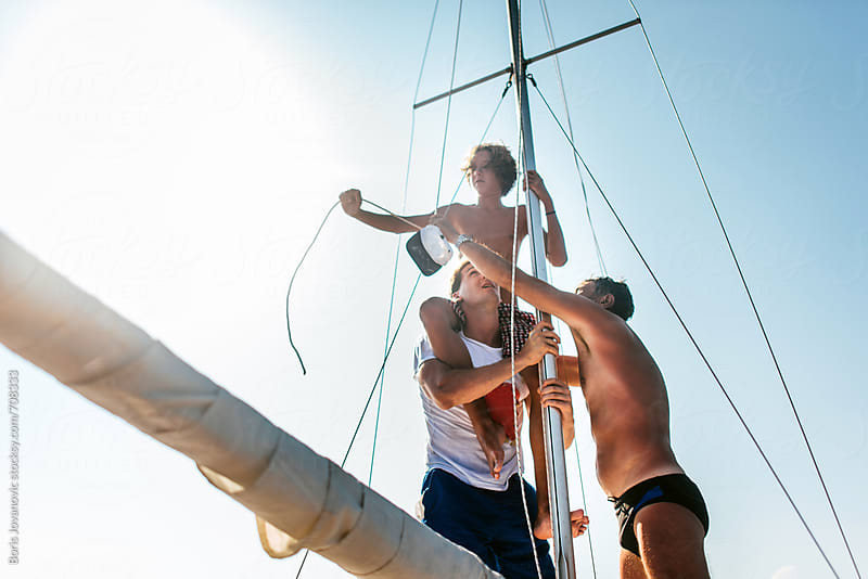 Sailors setting up a sail on the boat by Boris Jovanovic for Stocksy United