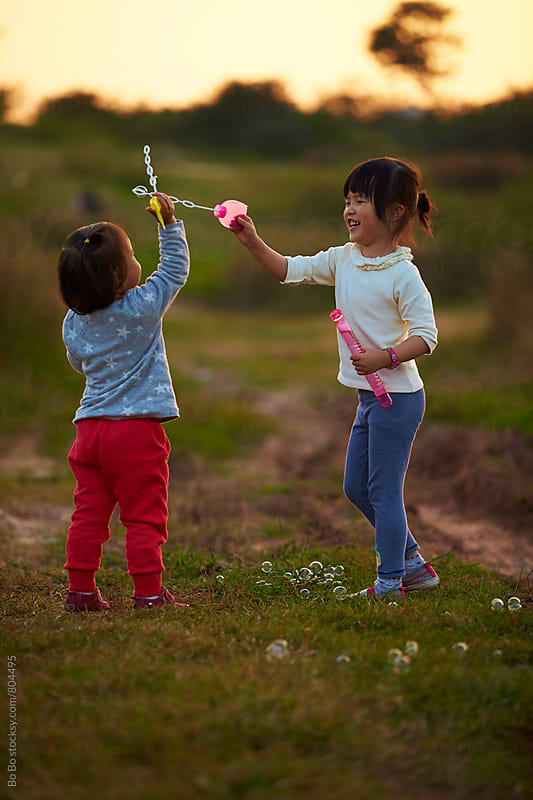 two happy asian little girl playing outdoor in the countryside by Bo Bo for Stocksy United