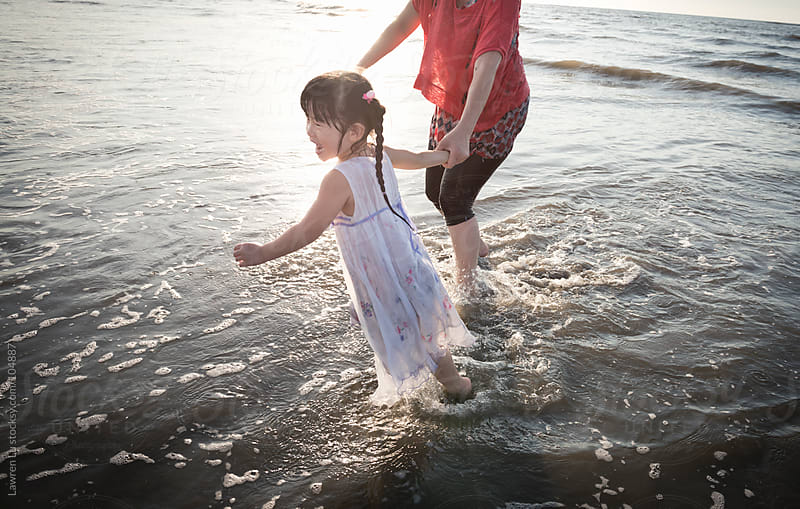 Little girl and mother playing with wave by Lawren Lu for Stocksy United