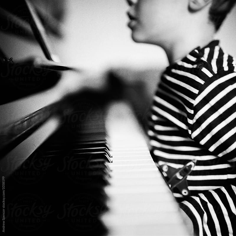 Child sat at the piano by Andrew Spencer for Stocksy United