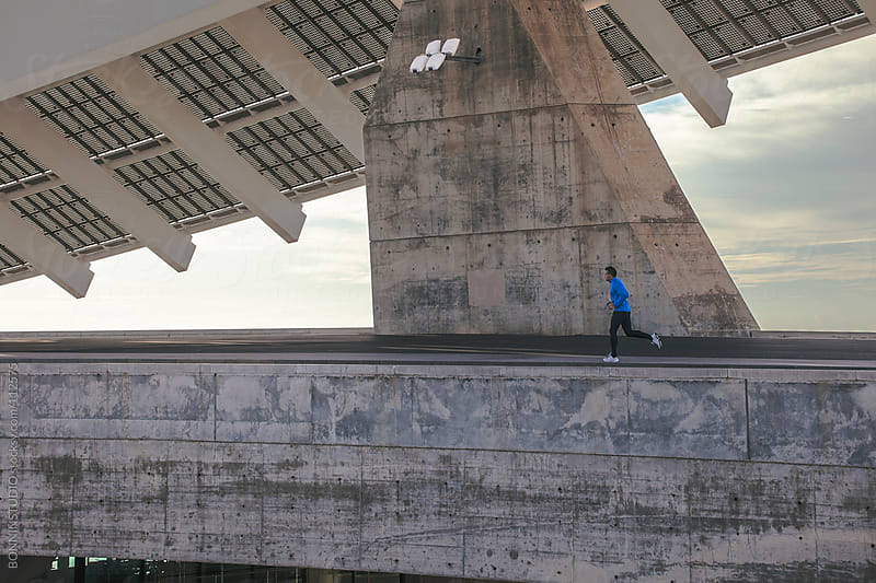 Man running and listenning music on big urban space.  by BONNINSTUDIO for Stocksy United