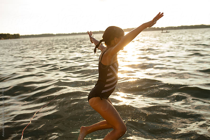 Energetic girl jumping into water by Amanda Worrall for Stocksy United