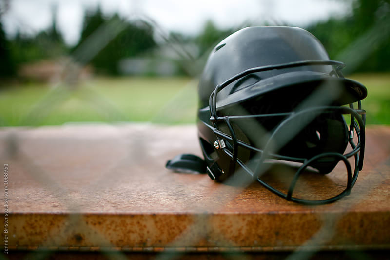 Softball helmet sits behind fence