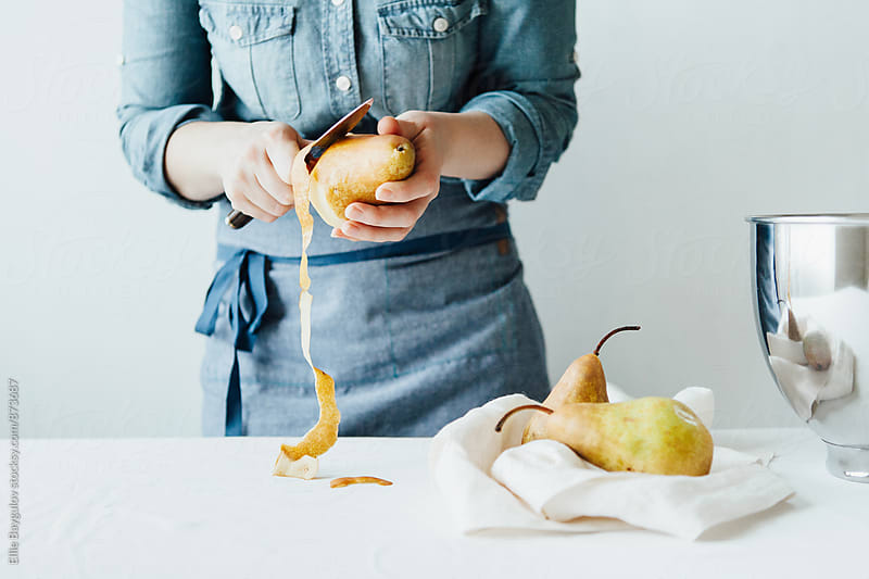 Woman pealing pears by Ellie Baygulov for Stocksy United
