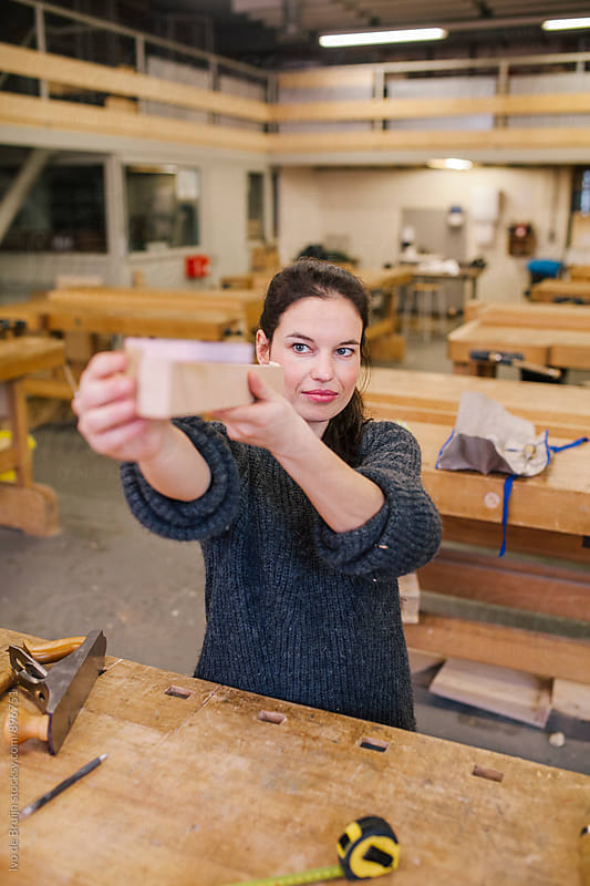 Female woodworker working on a bench , looking at a piece of wood by Ivo de Bruijn for Stocksy United