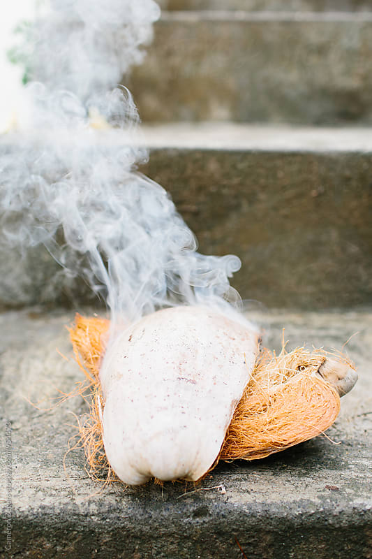 Balinese coconut husk burning to ward off evil spirits by Cameron Zegers for Stocksy United