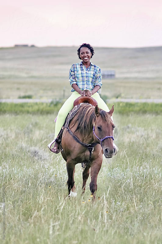 Black young woman on a horse by Per Swantesson for Stocksy United