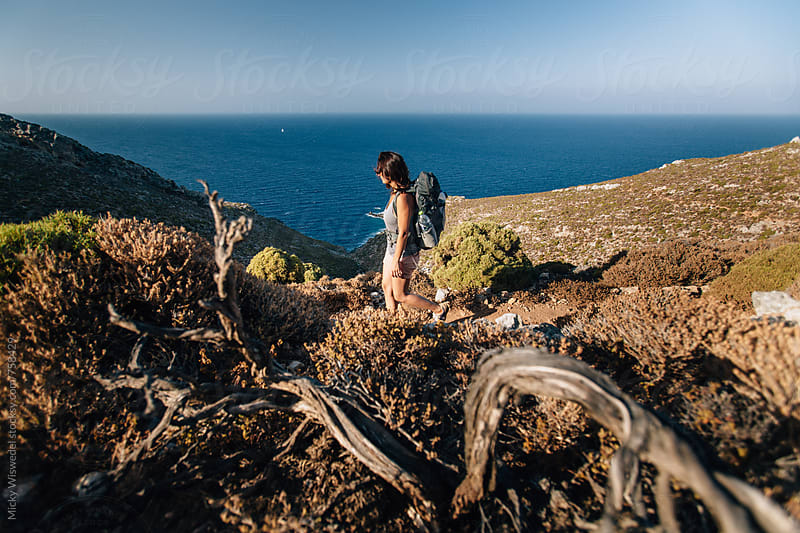 female hiker with backpack hiking along a rugged coast by Micky Wiswedel for Stocksy United
