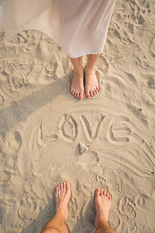 Couple Standing by 'Love' Written in the Sand by Lumina for Stocksy United