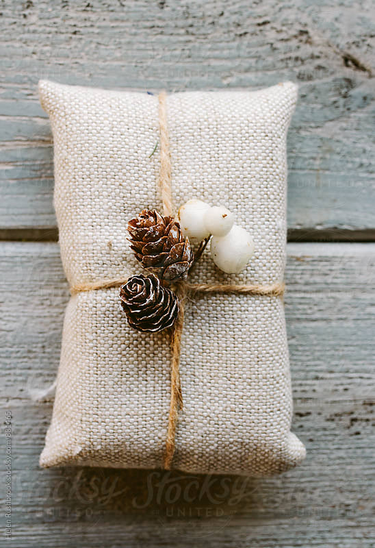 Christmas gift wrapped with linen and decorated with natural items. by Helen Rushbrook for Stocksy United