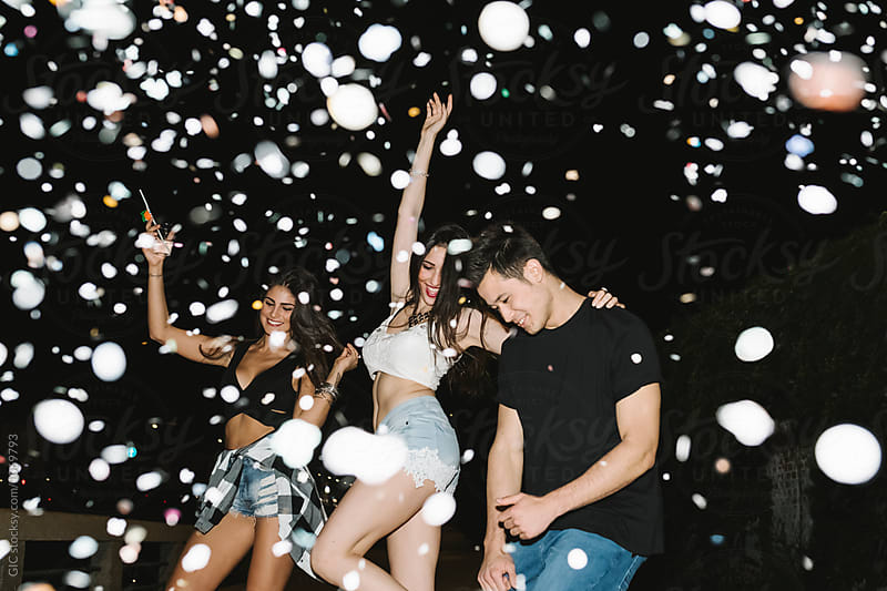 Friends dancing under a confetti rain during a night party by GIC for Stocksy United