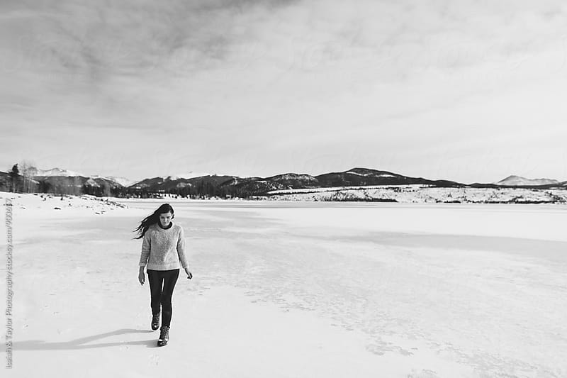 Woman walking on frozen lake by Isaiah & Taylor Photography for Stocksy United