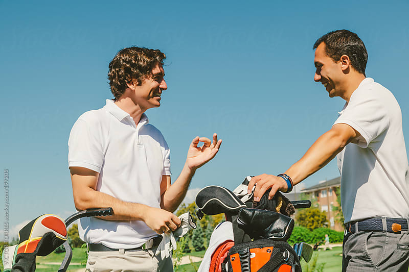 Two Friends Talking while a Brake During a Golf Game by VICTOR TORRES for Stocksy United