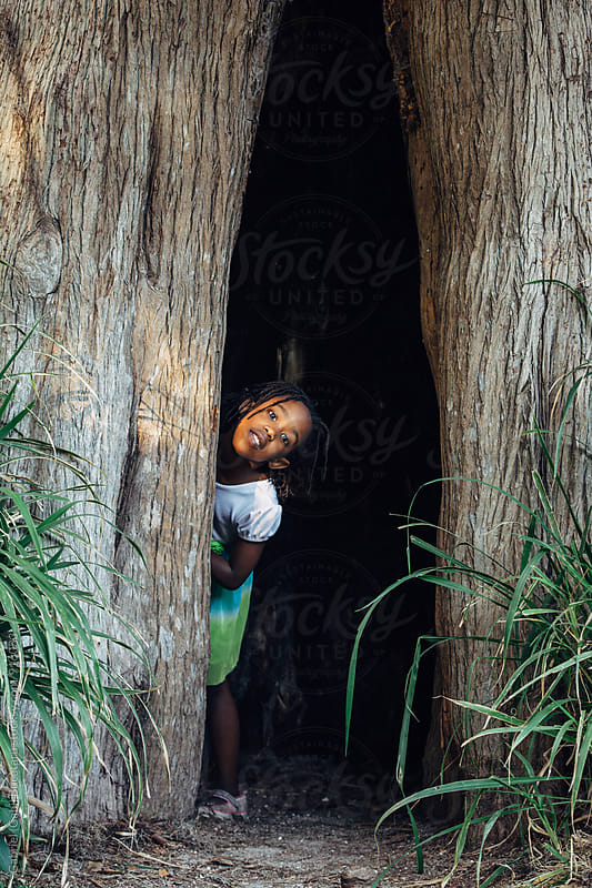 Black girl peeking out of an old tree hollow by Gabriel (Gabi) Bucataru for Stocksy United
