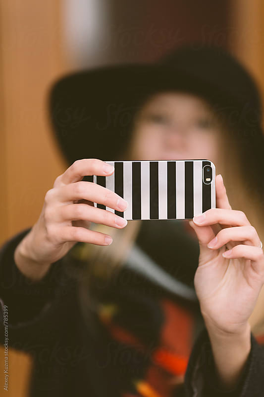 woman takes a selfie with the cell phone,selective focus  by Vesna for Stocksy United