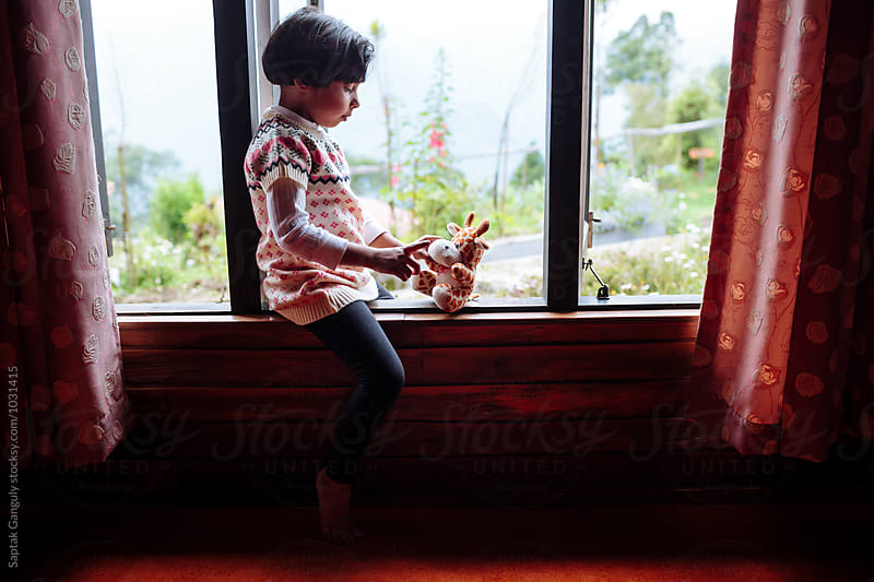 Little girl playing with her teddy by Saptak Ganguly for Stocksy United