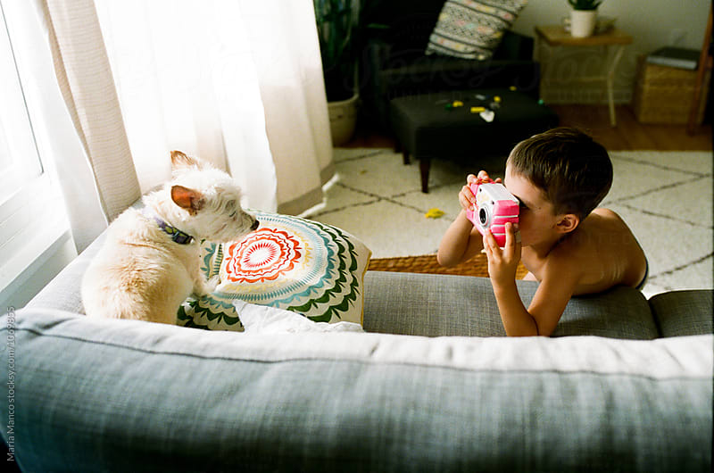boy takes photo of pet dog by Maria Manco for Stocksy United