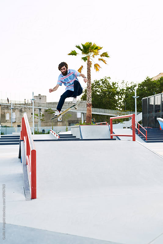Bearded tricker jumping on skateboard in skate park by Guille Faingold for Stocksy United