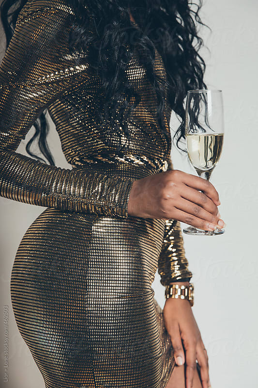 Closeup of black woman in golden dress holding a champagne glass by Lior + Lone for Stocksy United