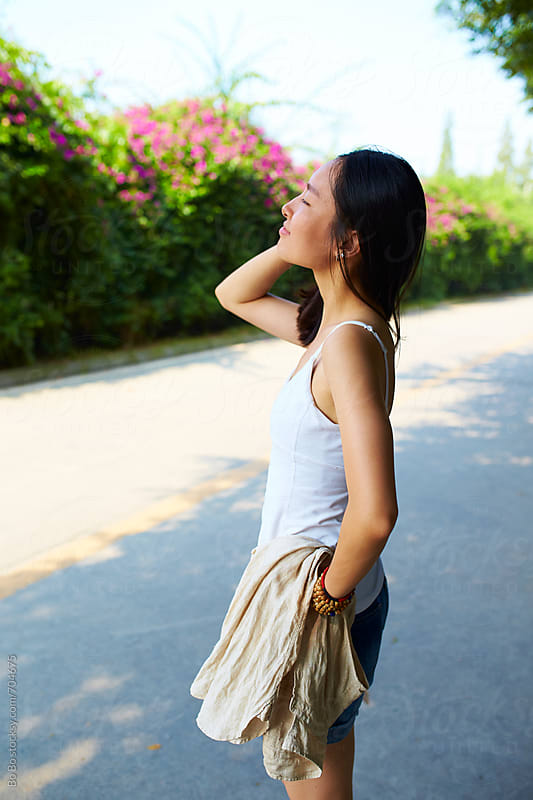 pretty young asian woman standing  outdoor by the road by Bo Bo for Stocksy United