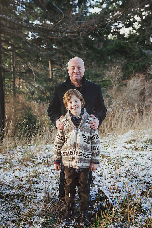 Happy grandpa enjoying his grandson outside in winter - fun portrait by Rob and Julia Campbell for Stocksy United