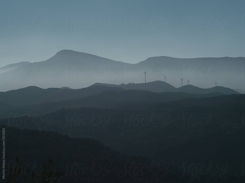 Wind power plants far awaywith mountains in the background by Martin Matej for Stocksy United