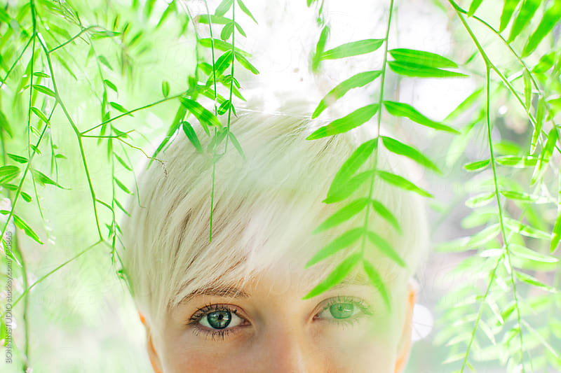 Closeup portrait of a blonde woman between green leaves. by BONNINSTUDIO for Stocksy United