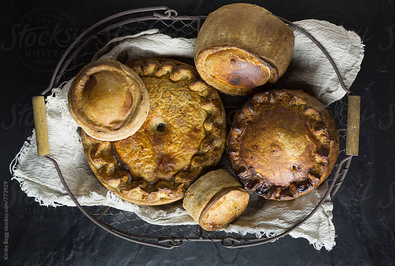 Various pork pies in a basket overhead by Kirsty Begg for Stocksy United