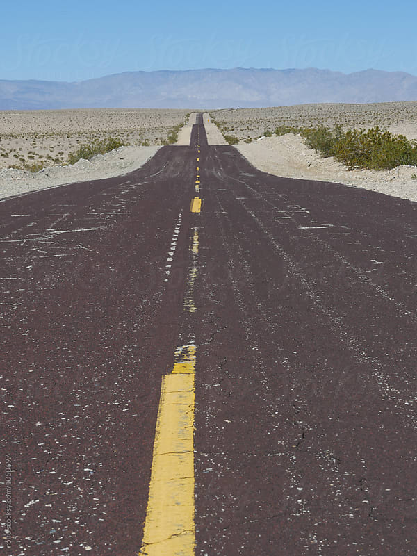 Black road with yellow marking in Death Valley,USA. by rolfo for Stocksy United