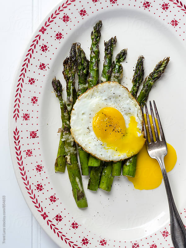 Close-up of fried egg with asparagus by Trent Lanz for Stocksy United