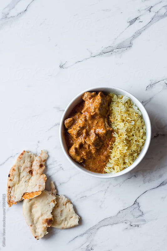 Indian curry with gobi naan and rice, in a white bowl on marble  by Gillian Vann for Stocksy United