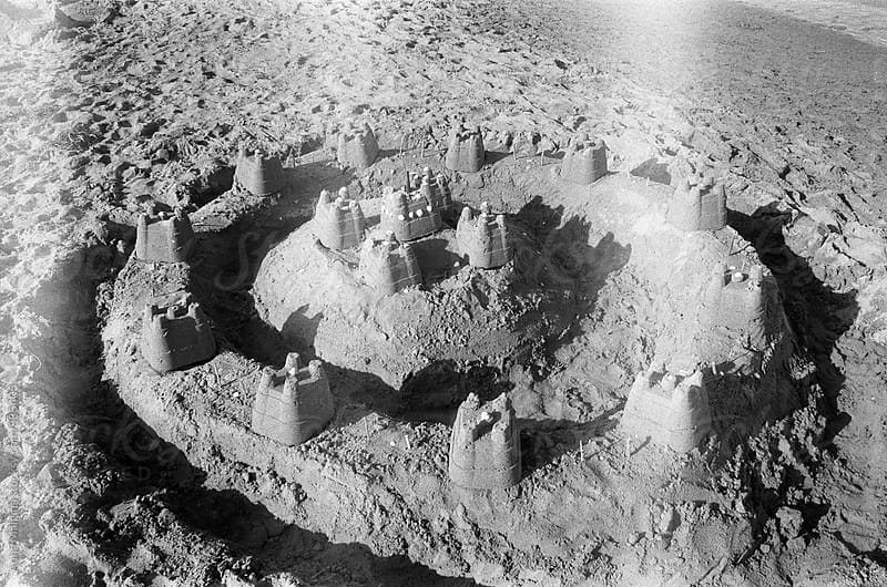 A black and white film photo of sand castle on the beach by Anna Malgina for Stocksy United