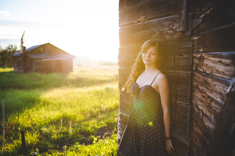 Young girl leaning on bard looking at camera with bright sunflare by Christian Tisdale for Stocksy United