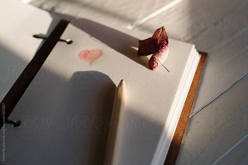 A notebook with a penciled heart, on a sunny desk. by Helen Rushbrook for Stocksy United