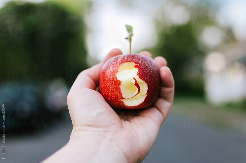Hand holding a red apple minus a bite by Deirdre Malfatto for Stocksy United