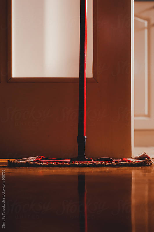 Red mop in the room on clean parquet by Dimitrije Tanaskovic for Stocksy United
