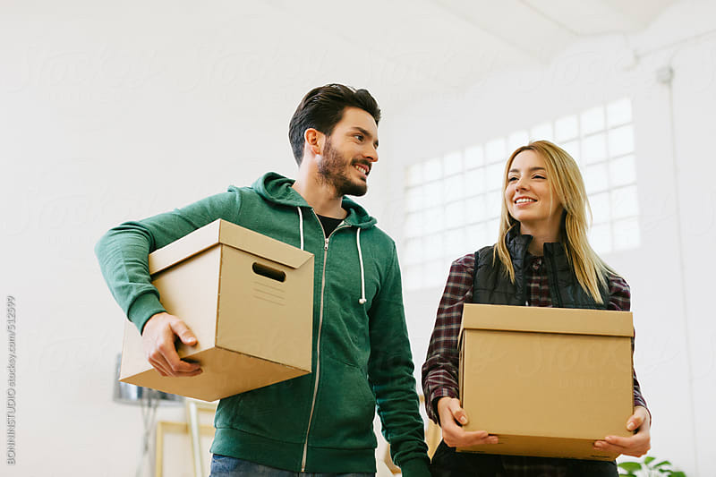 Young couple carrying cardboard boxes for moving into a new home.  by BONNINSTUDIO for Stocksy United