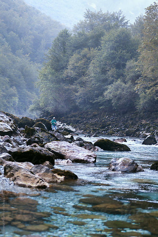 Man fishing early in the morning on a fast mountain river by Jovana Milanko for Stocksy United