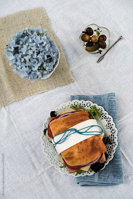 A deli styled wrapped sandwich with an olive an pickle bowl and a single blue hydrangea. by Rhonda Adkins for Stocksy United