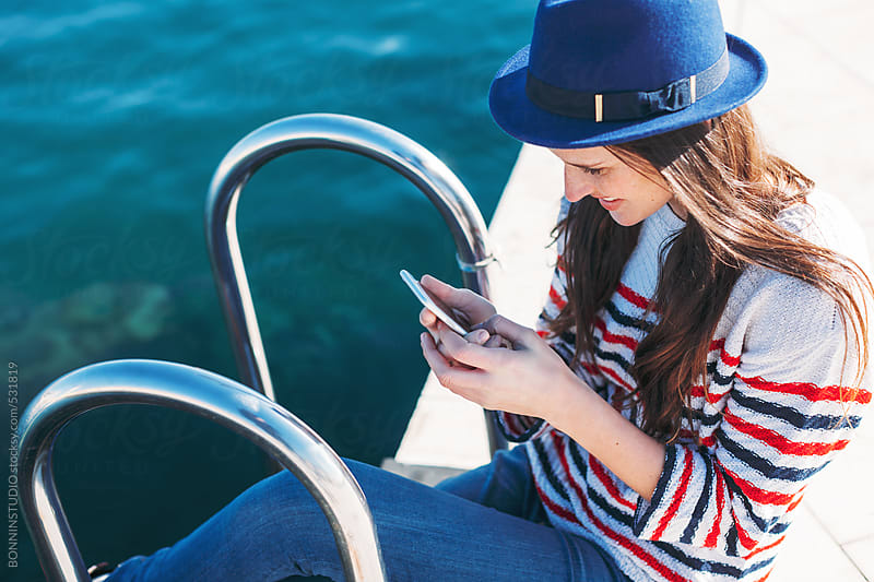 Young woman using phone sitting next to the sea.  by BONNINSTUDIO for Stocksy United