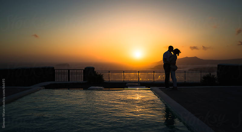 Couple kissing against sunset in Santorini by GIC for Stocksy United