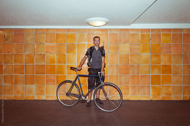 Bicycle Messenger Posing With His Bike by VISUALSPECTRUM for Stocksy United