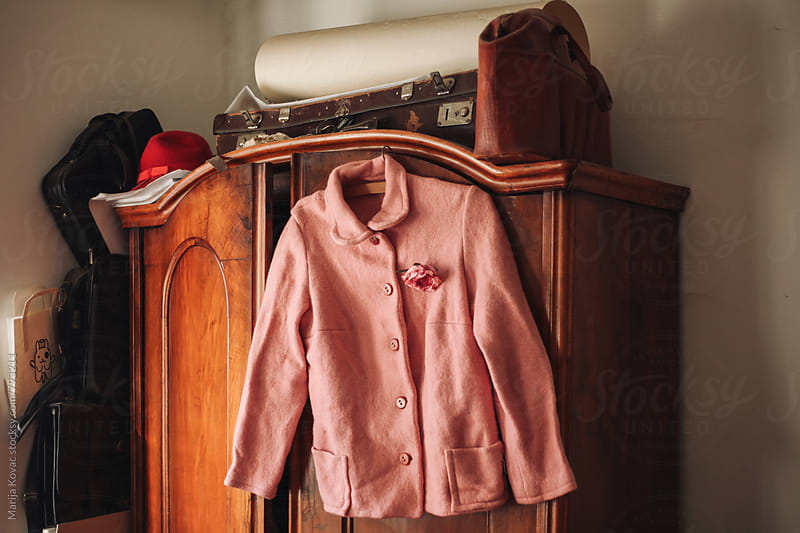 Pink jacket on a closet, horizontal by Marija Kovac for Stocksy United